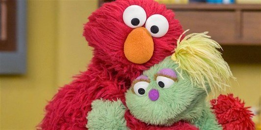 Karli new green puppet hugged by Elmo.