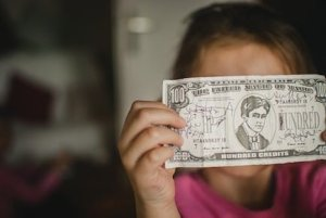 Child holding fake $100 bill over face.