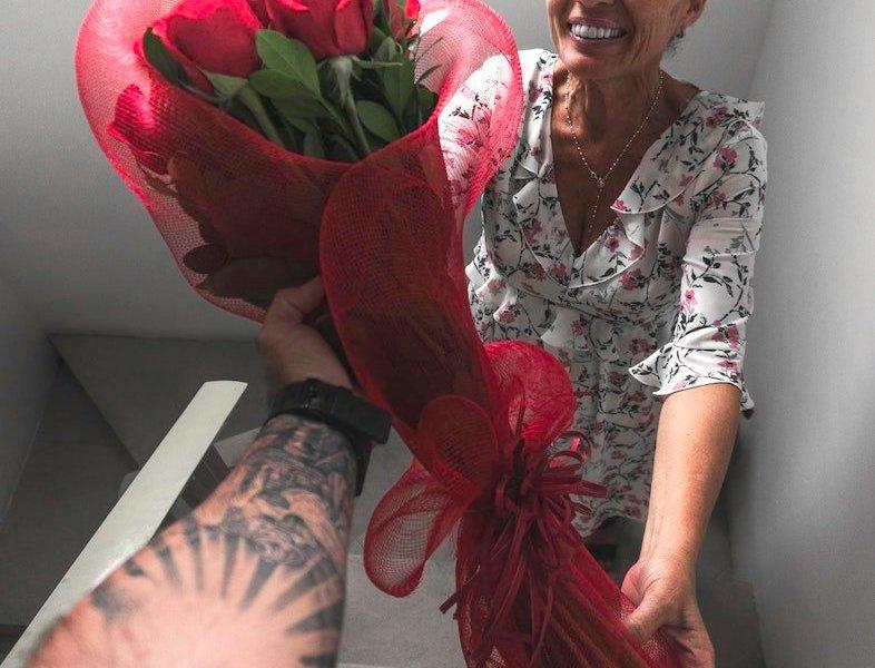 man handing mom flowers
