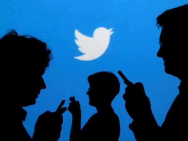 People holding mobile phones are silhouetted against a backdrop projected with the Twitter logo in this illustration picture taken in Warsaw September 27, 2013. REUTERS