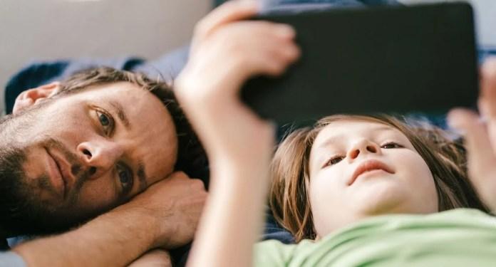 Pai e filha usando smartphone