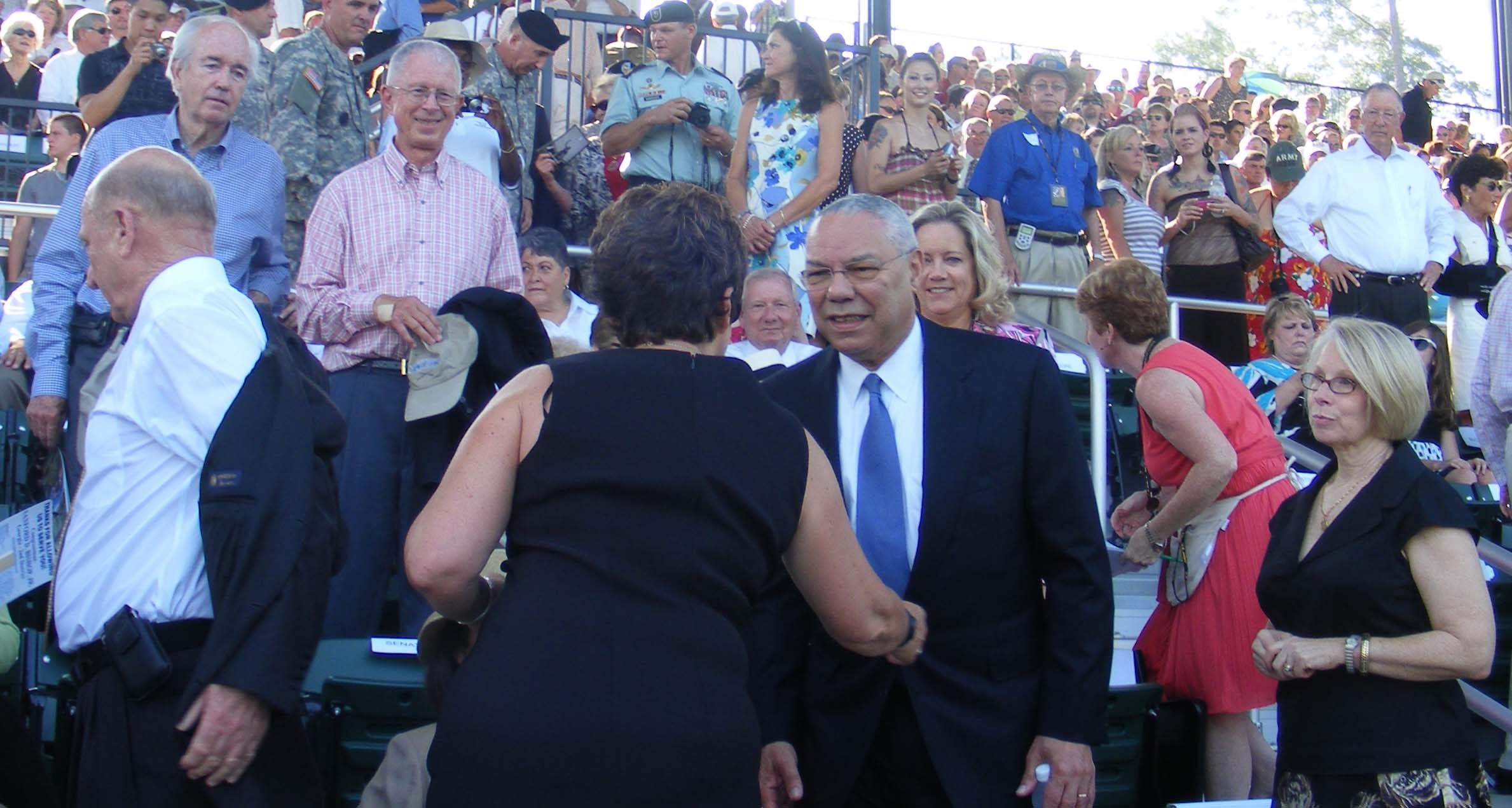 Museum director MG (R) Jerry White left removes coat,  former Sec. of State Colin Powell greets fellow attendee,  Parade Field stands, National Infantry Museum