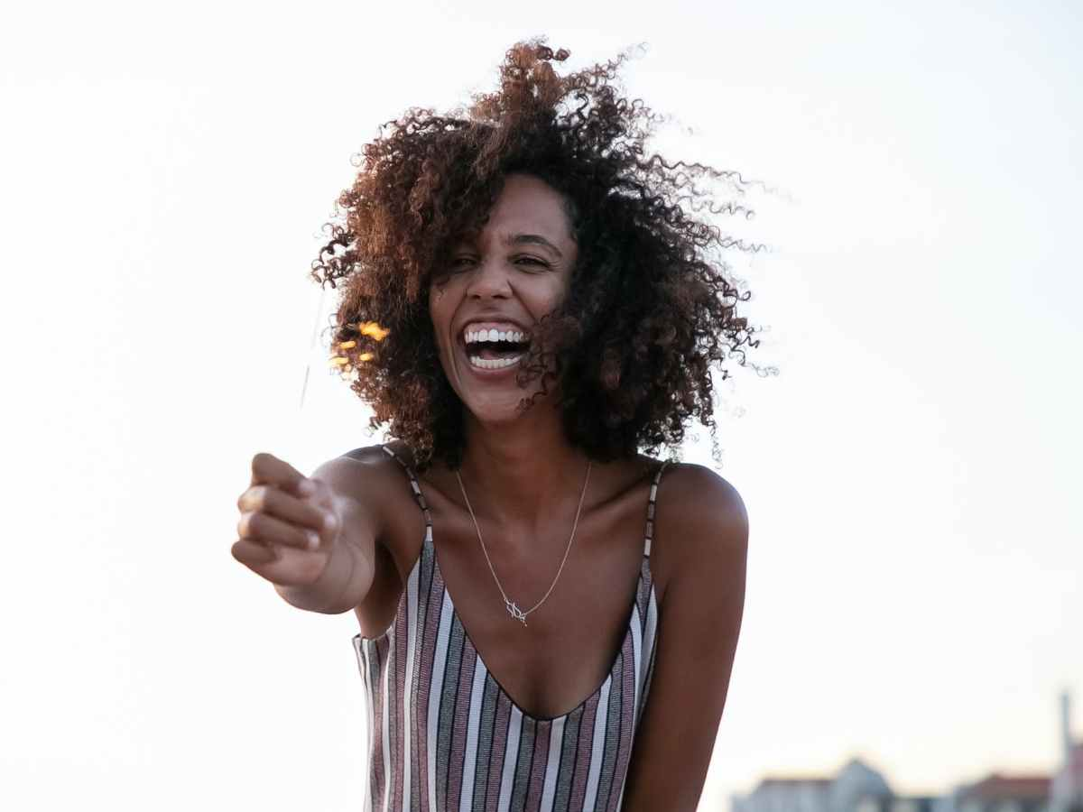 happy black woman with afro hairstyle and outstretched arm outdoors