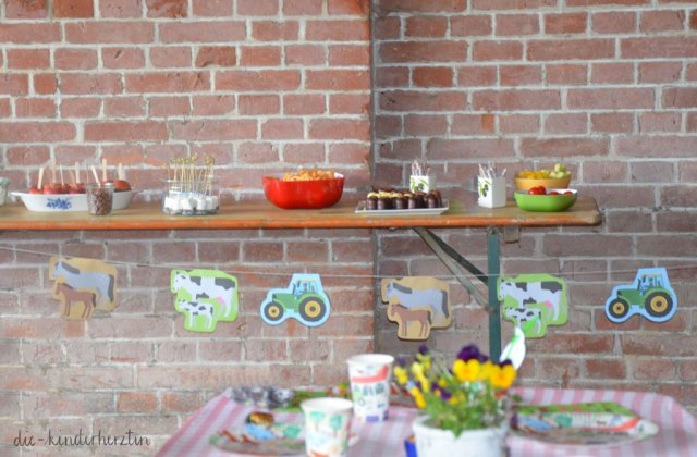 Mottoparty Bauernhof Kindergeburtstag Geburtstagstisch mit Tischdeko in der Scheune