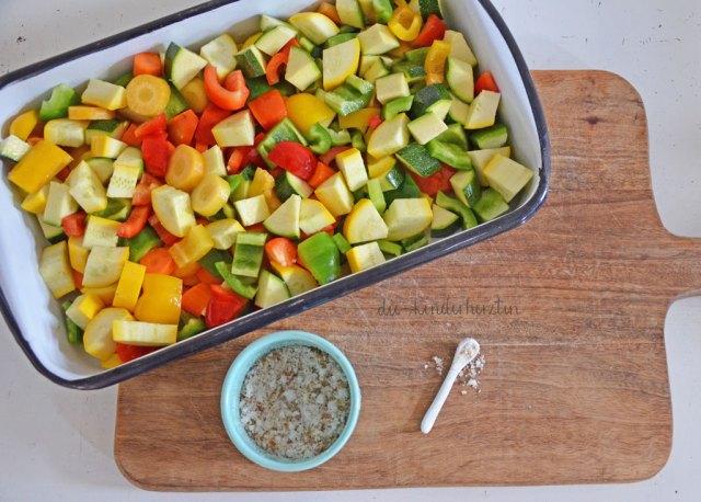 Zutaten für einen Ofengemüse-Nudel-Auflauf: buntes Gemüse in einer Auflaufform