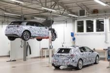 In der hell erleuchteten Werkstatthalle stehen zwei beklebte Prototypen. Die Probanden sind als Mercedes A-Klasse zu entlarven, doch Details über das Design sollen bis zur Weltpremiere Anfang Februar 2018 geheim bleiben. © Daimler