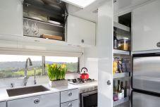 Mittig im Fahrzeug liegt die Küche, ausgestattet mit einem mannshohen Kühl- und Gefrierschrank. Zur üblichen Ausstattung zählen Gaskocher und Spüle, Backofen und Mikrowelle sowie ein Geschirrspüler. Foto: Auto-Medienportal.Net/Living Vehicle