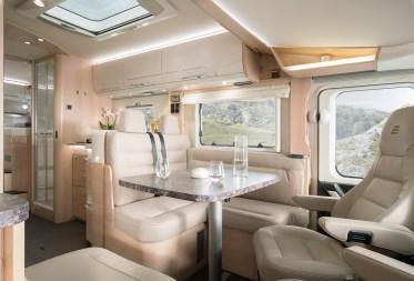 Der HYMER Panorama-Dachlüfter mit integrierter LED-Beleuchtung im Wohnraum sorgt für Frischluft und noch mehr Helligkeit. Hier abgebildet die Sitzgruppe im Hymermobil B-Klasse SupremeLine 704 mit der separaten Dusche mit Glastüre und den Längseinzelbetten im Heck. Foto: Hymer