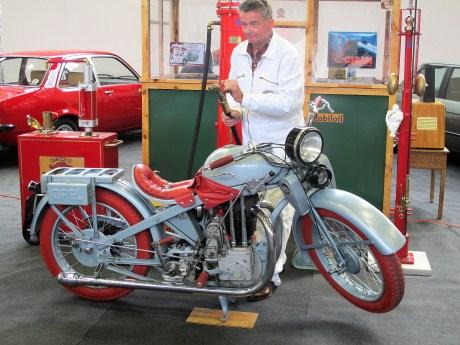 """Ein Opel-Motorrad Motoclub 500 von 1930 an einer """"polnischen"""" Tankstelle."""