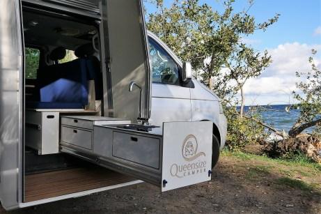 Ein zusätzlicher Einsatz im Mittelteil des Fahrzeugs nach außen schieben und bietet ein zweiflammiges Ceran-Gaskochfeld, Spüle sowie Schubladen für Besteck und Kochutensilien. Foto: Auto-Medienportal.Net/Queensize Camper