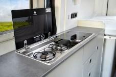"""Auf der Beifahrerseite residiert die Küchenzeile, die außer einem zweiflammigen Gasherd und einem 70 Liter fassenden Kühlschrank auch eine Vielzahl an Staufächern und Arbeitsflächen bietet. © """"obs/Ford-Werke GmbH/Ford / Westfalia"""""""