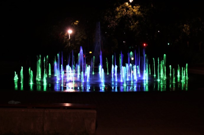 Bei einsetzender Dunkelheit zieht im Park der Stadt Torun eine musikalisch untermalte Illumination am Brunnen die Menschen in ihren Bann. © Kurt Sohnemann