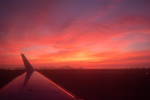 Bright pink sunset from the window seat of a plane in Lima