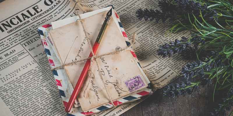shallow focus photo of mail envelope on newspaper