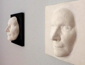 Zwei Totenmasken mit unterschiedlichem Hintergrund
