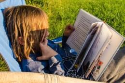 Foto von Luis, der in der Abendsonne ein Buch ansieht.