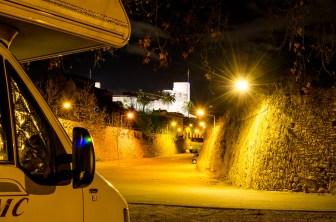 Foto mit dem vorderem Teil eines Wohnmobils mit Sicht auf den Ort El Catllar bei Dunkelheit.