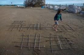 Foto eines Kindes, das gerade aus Schilfrohr einen Käfig bauen will.