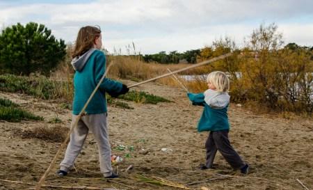 Foto von zwei Kindern, die mit Schilfrohren als Schwertern miteinander kämpfen.