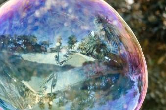 Foto einer Riesenseifenblase , in der sich die Promenade samt Fotograf in Alicante spiegelt.