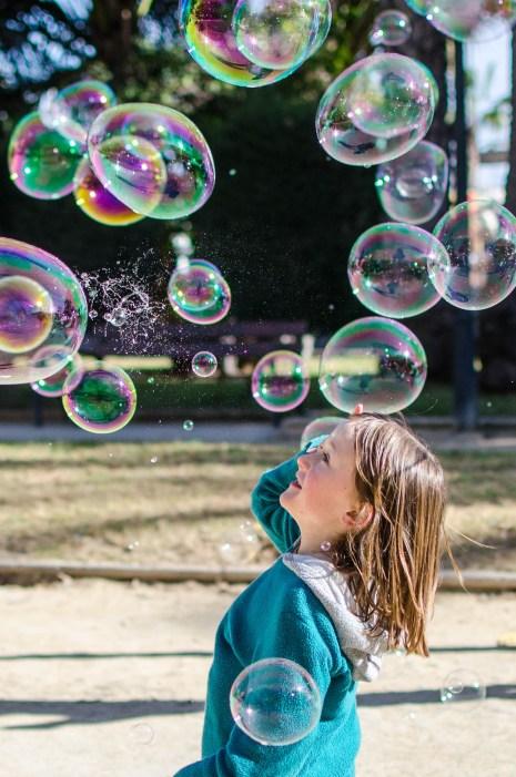 Foto von vielen Seifenblasen mit einem Kind.