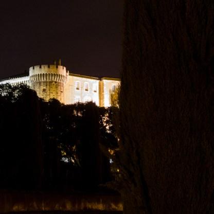 Foto der Burg in Suze-la-Rousse bei Nacht.