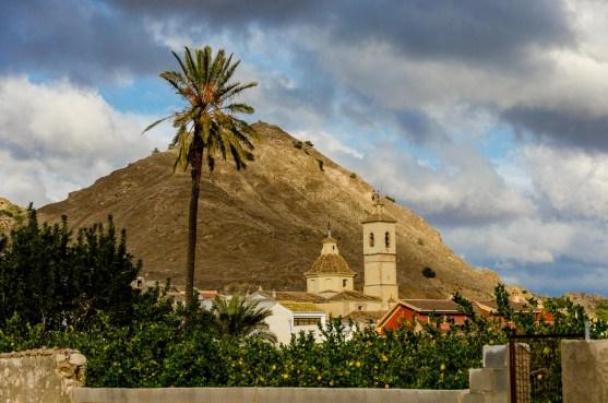 Foto von einer Kirche, Palme und Berg im Hintergrund.
