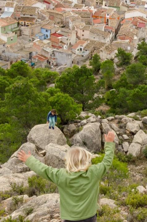 Foto von zwei Kindern beim Klettern auf Felsen mit Blick auf die Dächer von Ricote.