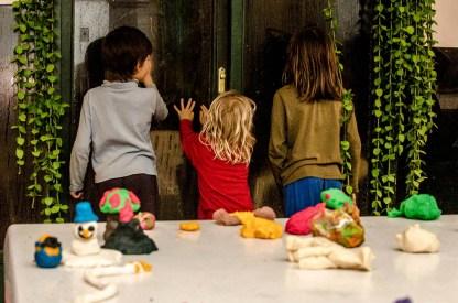Foto von Kindern, die an der Tür in den Regen hinaussehen.
