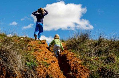 Foto von zwei Kindern, die gerade einen Hügel hoch steigen.