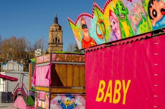 Foto von Volksfestbuden mit Kirche im Hintergrund.
