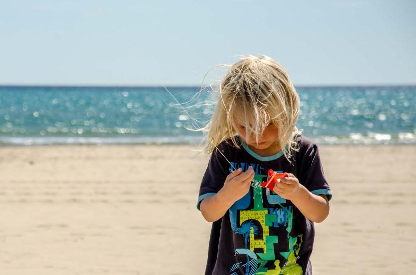 Kind am Strand hält eine Drachenschnur.