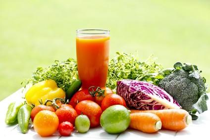 野菜や果物の間にグラスに入ったオレンジ色の野菜ジュース