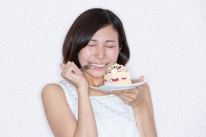 ケーキを食べて喜んでいる女性