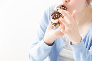 クリームが入ったドーナツを食べる女性