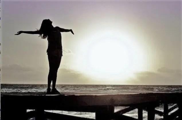 femme libre sur un ponton les bras ouvert devant un coucher de soleil elle a chasser le stress et est heureuse