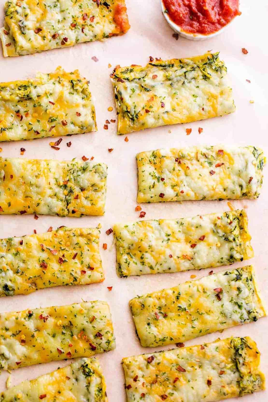 overhead shot of eleven cheesy keto zucchini breadsticks with marinara sauce on the side