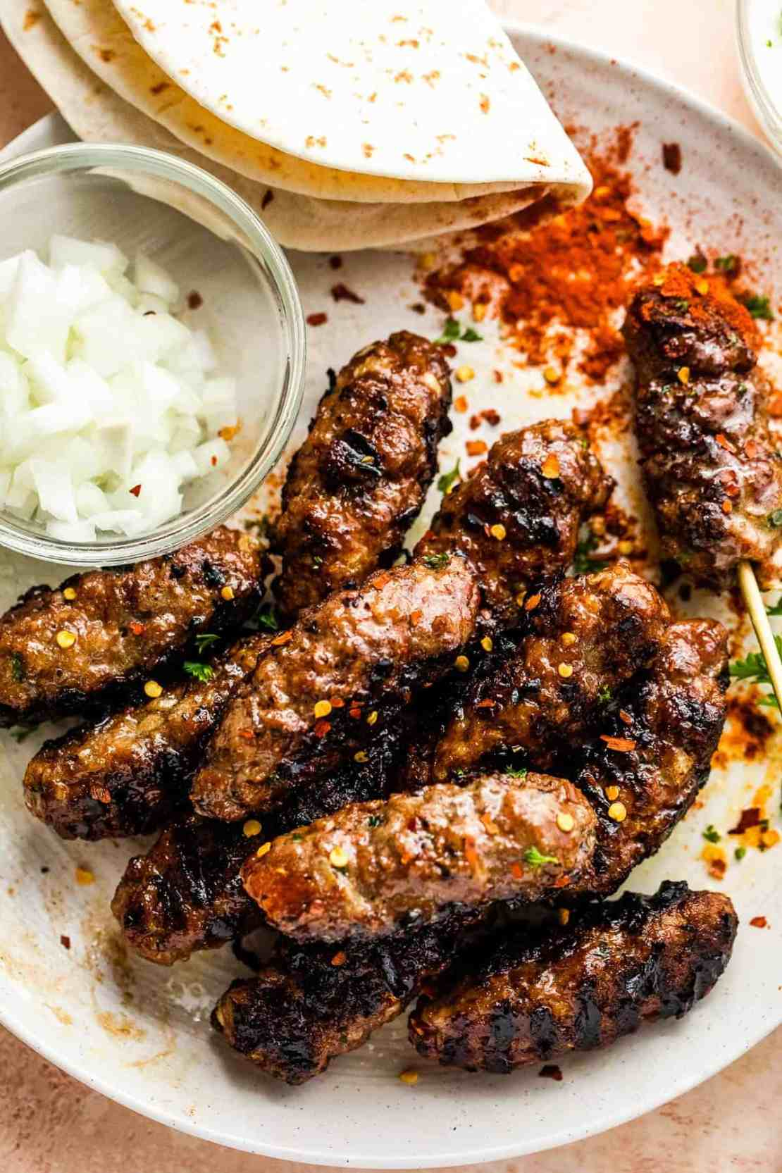 served kebabs with chopped onions and crushed pepper