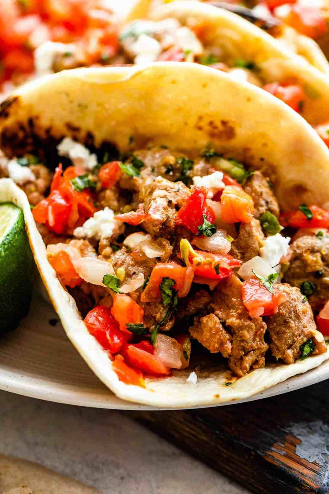 one pork carnitas taco topped with tomatoes and onions