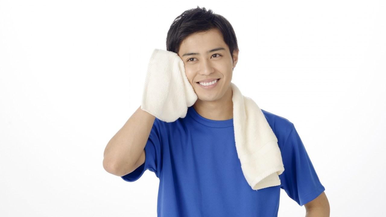 汗を気持ちよくタオルで拭く男性