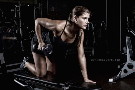 Fit woman performing dumbbell rows