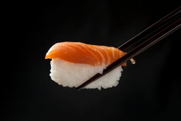 Salmon sushi with black chopsticks on a black background