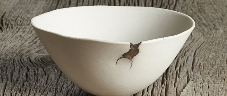 White ceramic bowl with a chipped rim on a wooden table surface