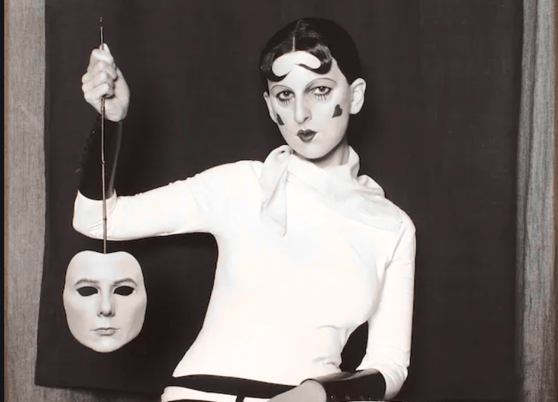 Black and white photo of a woman taking of her mask