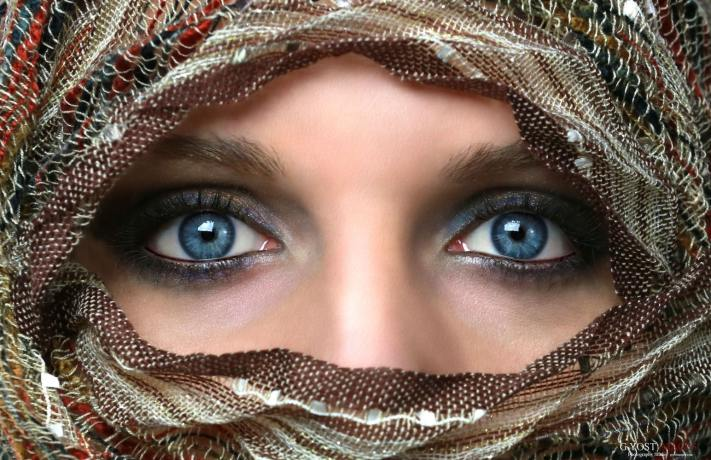 A blue eyed woman wearing a head cover