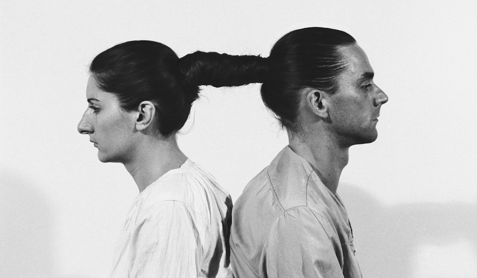 Black and white photo of a man and a woman connected with their hair - performance art by Marina Abramovic