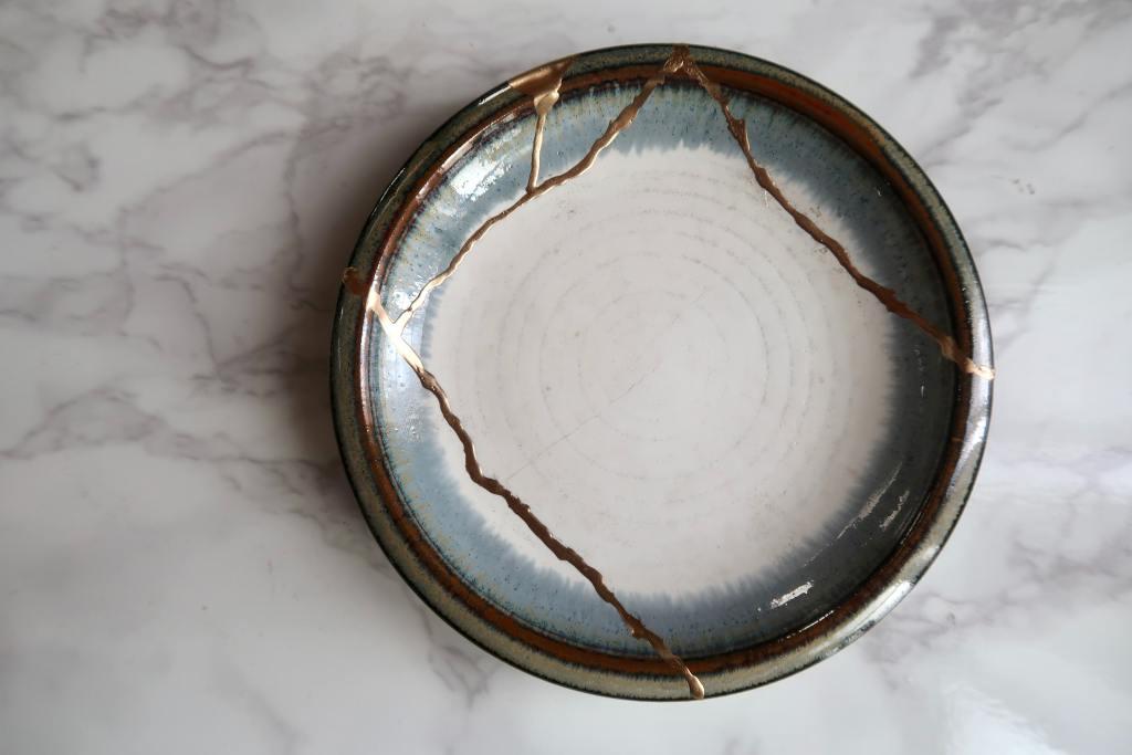 Kintsugi ceramic plate with a golden powder and a glue