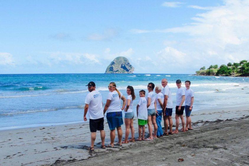 Des plongeurs et plongeuses de tous âges sont au bord d'une plage
