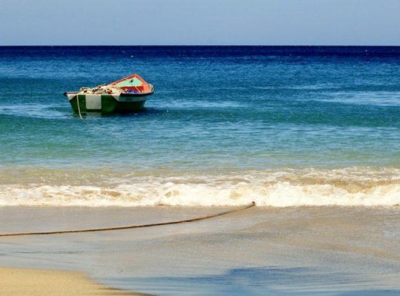 Plonger en Martinique permet de voir de beaux paysages comme cette plage avec le bateau de pêcheur amarré.