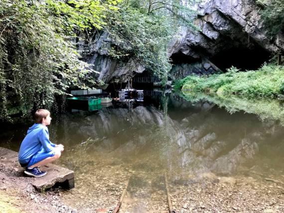 Un enfant regarde un plan d'eau à l'entrée d'une grotte